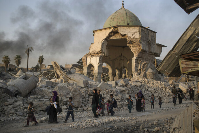 FILE - In this July 4, 2017, file photo, fleeing Iraqi civilians walk past the heavily damaged al-Nuri mosque as Iraqi forces continue their advance against Islamic State militants in Iraq's Old City of Mosul. The United Nations' cultural agency says reconstruction of Al-Nouri Mosque in Iraq's city of Mosul is scheduled to start at the beginning of 2020.  (AP Photo/Felipe Dana, File)