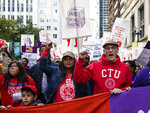 In this Oct. 14, 2019 photo, Chicago Teachers Union President Jesse Sharkey, center right, and Vice President Stacy Davis Gates, center, left, march with members of the CTU and SEIU Local 73 through the Loop after a rally, three days before the unions could walk off the job on strike. Chicago's public schools have canceled classes after the teachers' union president announced that his bargaining team will recommend teachers vote to go on strike. Mayor Lori Lightfoot said Wednesday, Oct. 16, 2019, that classes would be canceled Thursday after determining that she can't accept the Chicago Teachers Union's demands, which she says would cost the city $2.5 billion it can't afford. (Ashlee Rezin Garcia/Chicago Sun-Times via AP)
