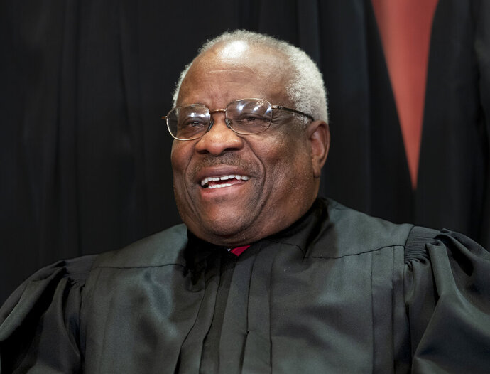 FIILE - In this Nov. 30, 2018, file photo, Supreme Court Associate Justice Clarence Thomas, appointed by President George H. W. Bush, sits with fellow Supreme Court justices for a group portrait at the Supreme Court Building in Washington. Thomas has never been afraid to turn right when his colleagues turn left, or in any direction really as long as there's a place to plug in his 40-foot refitted tour bus. (AP Photo/J. Scott Applewhite, File)