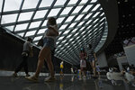 People wearing face masks to help curb the spread of the coronavirus visit a shopping mall in Beijing, Sunday, June 6, 2021. (AP Photo/Andy Wong)