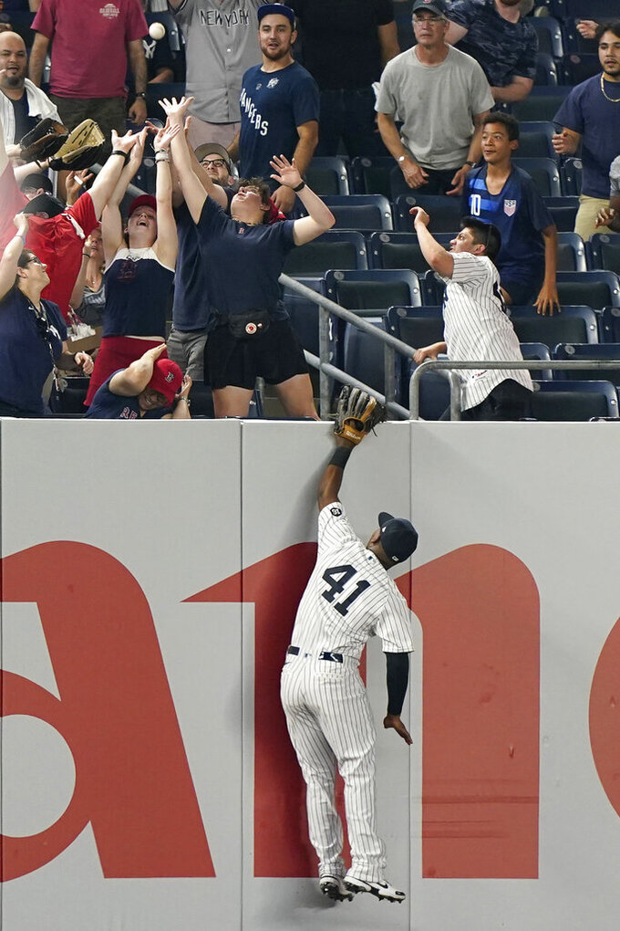 Fans reach for Marwin Gonzalez's game-tying, two-run home run as New York Yankees left fielder Miguel Andujar (41) leaps in vain during the seventh inning of a baseball game against the Boston Red Sox, Sunday, June 6, 2021, at Yankee Stadium in New York. (AP Photo/Kathy Willens)