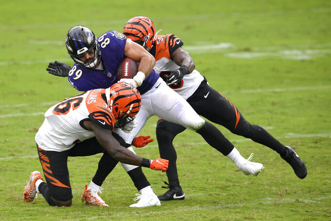 Baltimore Ravens tight end Mark Andrews (89) is tackled by Cincinnati Bengals strong safety Shawn Williams (36) and linebacker Akeem Davis-Gaither during the first half of an NFL football game, Sunday, Oct. 11, 2020, in Baltimore. (AP Photo/Nick Wass)