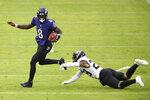 Baltimore Ravens quarterback Lamar Jackson (8) avoids a sack attempt by Jacksonville Jaguars safety Josh Jones (29) during the second half of an NFL football game, Sunday, Dec. 20, 2020, in Baltimore. (AP Photo/Nick Wass)