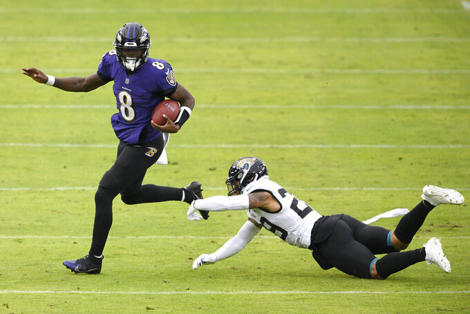 Baltimore Ravens quarterback Lamar Jackson (8) avoids a sack attempt by Jacksonville Jaguars safety Josh Jones (29) during the second half of an NFL football game, Sunday, Dec. 20, 2020, in Baltimore. (AP Photo/Nick Wass)
