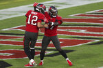 Tampa Bay Buccaneers running back Ronald Jones III (27) celebrates with quarterback Tom Brady (12) after scoring on a 37-yard touchdown pass during the first half of an NFL football game against the Kansas City Chiefs Sunday, Nov. 29, 2020, in Tampa, Fla. (AP Photo/Mark LoMoglio)