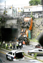 First responders work the scene of a truck accident in Union, City, N.J., not far from the Lincoln Tunnel, Wednesday, July 3, 2019. The overturned garbage truck blocked a major route out of New York City during the evening commute before the Fourth of July weekend. (Joe Shine/The Jersey Journal via AP)