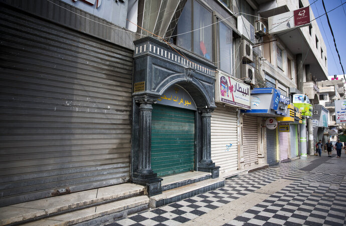 Palestinians walk next to closed shops in Gaza City, Tuesday, June 25, 2019, during a general strike against this week's economic conference in Bahrain that will kick off the Trump administration's plan for Mideast peace. (AP Photo/Khalil Hamra)