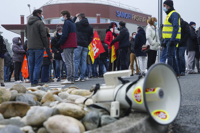 Striking workers gather outside the French pharmaceutical company Sanofi headquarters in Marcy l'Etoile, central France, Tuesday, Jan.19, 2021. Employees of pharmaceutical company Sanofi stage a protest against planned redundancies that they say could slow the fight against the Coronavirus pandemic . Sanofi had been developing Covid vaccines but will not be ready to roll out until late 2021. (AP Photo/Laurent Cipriani)