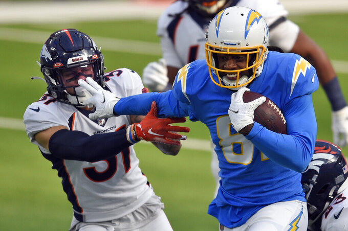 Los Angeles Chargers wide receiver Mike Williams, right, runs past Denver Broncos defensive back P.J. Locke during the first half of an NFL football game Sunday, Dec. 27, 2020, in Inglewood, Calif. (AP Photo/Kelvin Kuo)