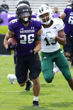 Northwestern running back Evan Hull runs with the ball past Ohio cornerback John Gregory during the second half of an NCAA college football game in Evanston, Ill., Saturday, Sept. 25, 2021. Northwestern won 35-6. (AP Photo/Nam Y. Huh)