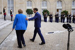 France's President Emmanuel Macron, right, and German Chancellor Angela Merkel leave after a joint press conference, at the Elysee Palace, in Paris, Thursday, Sept. 16, 2021. (AP Photo/Michel Euler)