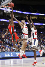 Georgia guard Jordan Harris (2) drives past Mississippi defenders KJ Buffen (5) and Sammy Hunter (23) in the first half of an NCAA college basketball game in the Southeastern Conference Tournament Wednesday, March 11, 2020, in Nashville, Tenn. (AP Photo/Mark Humphrey)