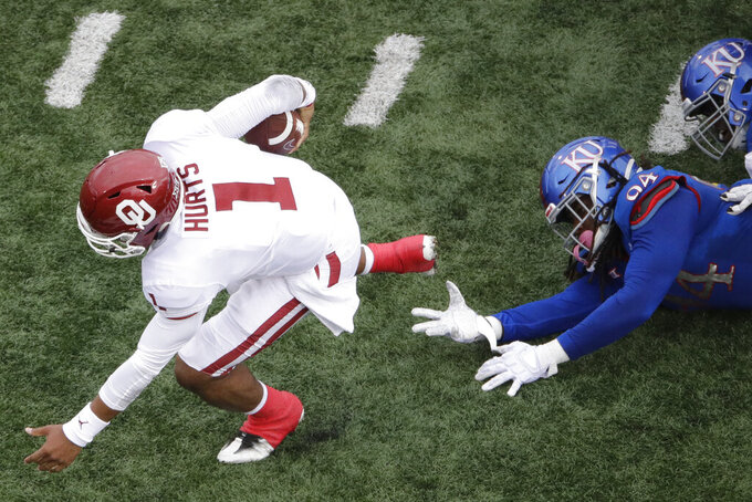 Oklahoma quarterback Jalen Hurts (1) gets past Kansas defensive end Codey Cole III (94) as he runs the ball during the first half of an NCAA college football game Saturday, Oct. 5, 2019, in Lawrence, Kan. (AP Photo/Charlie Riedel)