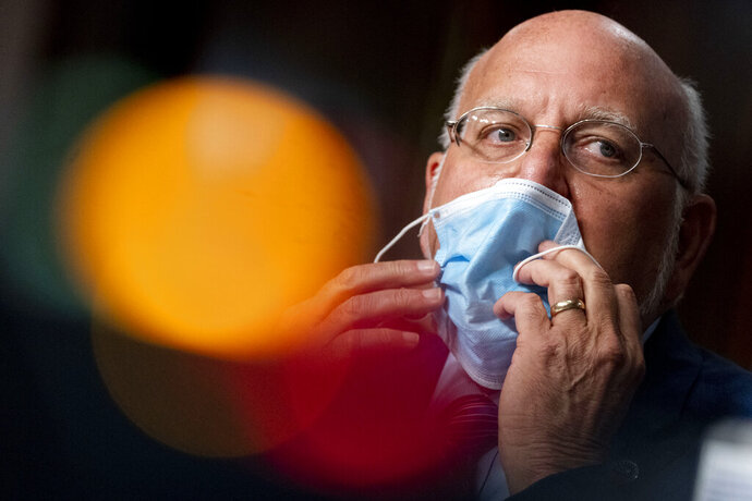 FILE - In this Wednesday, Sept. 16, 2020, file photo, Centers for Disease Control and Prevention Director Dr. Robert Redfield puts his mask back on after speaking at a Senate Appropriations subcommittee hearing on a
