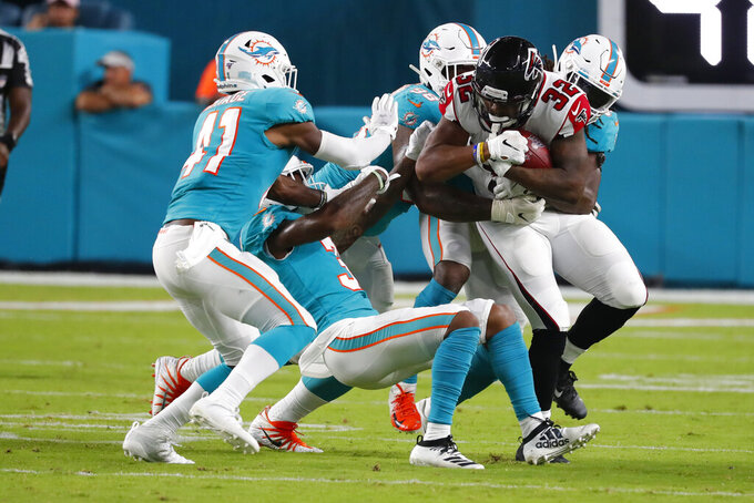 Atlanta Falcons running back Qadree Ollison (32) is stopped by several Miami Dolphins, incuding defensive back Montre Hartage (41), during the second half of a preseason NFL football game Thursday, Aug. 8, 2019, in Miami Gardens, Fla. (AP Photo/Wilfredo Lee)