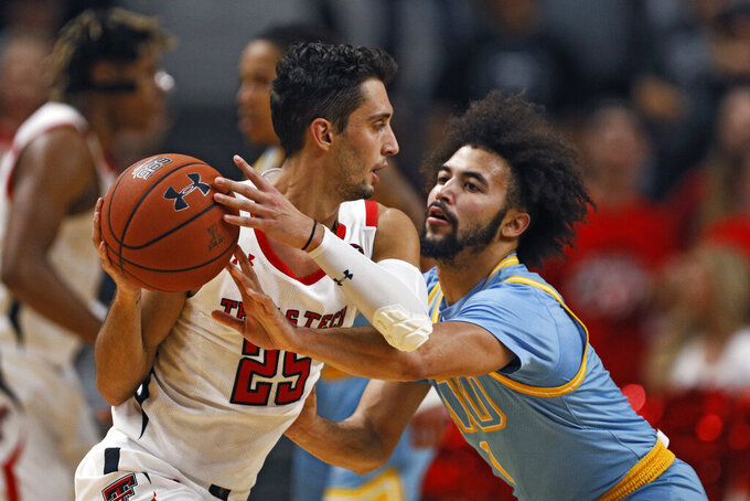 Long Island's Julian Batts (1) knocks the ball away from Texas Tech's Davide Moretti (25) during the first half of an NCAA college basketball game Sunday, Nov. 24, 2019, in Lubbock, Texas. (AP Photo/Brad Tollefson)