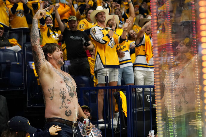 Tennessee Titans NFL football offensive lineman Taylor Lewan celebrates after a goal by the Nashville Predators during the second period in Game 4 of an NHL hockey Stanley Cup first-round playoff series between the Predators and the Carolina Hurricanes Sunday, May 23, 2021, in Nashville, Tenn. (AP Photo/Mark Humphrey)
