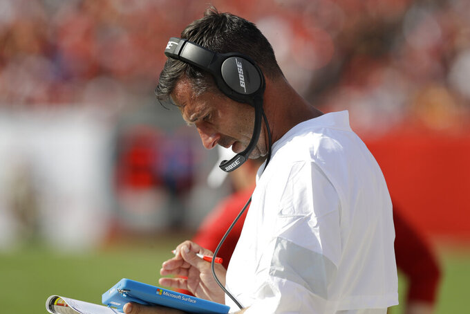 San Francisco 49ers head coach Kyle Shanahan reads on the sidelines against the Tampa Bay Buccaneers during the first half an NFL football game, Sunday, Sept. 8, 2019, in Tampa, Fla. (AP Photo/Chris O'Meara)