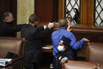 """FILE - In this Jan. 6, 2021, file photo U.S. Capitol Police officers with guns drawn and Rep. Troy Nehls, R-Texas, in blue shirt, watch as insurrections loyal to President Donald Trump try to break into the House Chamber at the U.S. Capitol in Washington. First, some blamed the deadly Jan. 6 attack on the Capitol on left-wing Antifa antagonists, a theory quickly debunked. Then came comparisons of the rioters as peaceful protesters, or even """"tourists."""" Now, Trump allies rallying in support of those people charged in the Capitol riot are calling them """"political prisoners,"""" a stunning effort to revise the narrative of that deadly day. (AP Photo/J. Scott Applewhite, File)"""