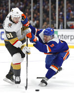 New York Islanders defenseman Adam Pelech (3) holds on to Vegas Golden Knights center Jonathan Marchessault (81) after breaking his stick during the first period of an NHL hockey game Thursday, Dec. 5, 2019, in Uniondale, N.Y. (AP Photo/Kathy Willens)