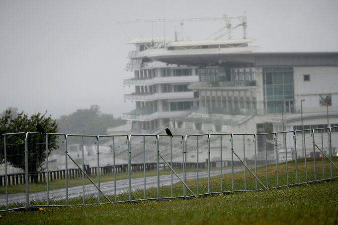 A crow sits on fencing erected around the Epsom Downs racecourse, in Epsom, England, Tuesday, June 30, 2020. The Derby annual horse race will take place behind closed doors on Saturday amid the coronavirus pandemic. (AP Photo/Matt Dunham)