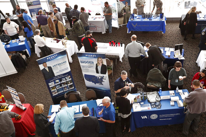 FILE - In this March 7, 2019, photo visitors to the Pittsburgh veterans job fair meet with recruiters at Heinz Field in Pittsburgh. Veterans and active service members can get help starting or running a business from programs sponsored by the federal government and private groups. (AP Photo/Keith Srakocic, File)