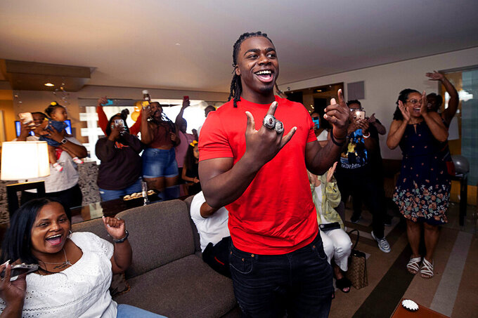Oklahoma running back Rhamondre Stevenson, center, is congratulated by family and friends in a suite at the Aria Resort in Las Vegas, Saturday, May 1, 2021, after he was selected in the fourth round of the NFL football draft by the New England Patriots. (Steve Marcus/Las Vegas Sun via AP)