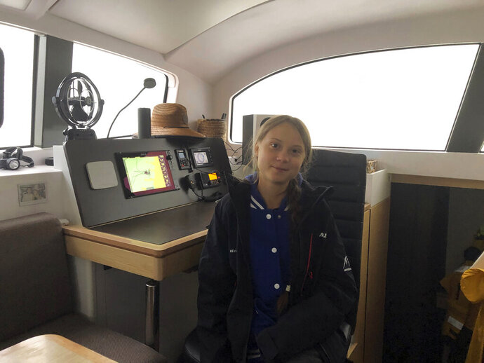Greta Thunberg, a 16-year-old climate activist from Sweden, sits on a catamaran docked in Hampton, Va., on Tuesday, Nov. 12, 2019. Thunberg will leave North America and begin her return trip across the Atlantic on Wednesday aboard a 48-foot (15-meter) catamaran sailboat whose passengers include an 11-month-old baby. The boat leaves little to no carbon footprint, boasting solar panels and a hydro-generators for power. (AP Photo/Ben Finley)