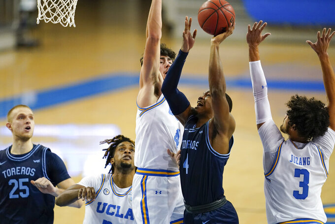 San Diego forward Josh Parrish (4) goes up for a shot between UCLA guards Jaime Jaquez Jr. (4) and Johnny Juzang (3) during the first half of an NCAA college basketball game Wednesday, Dec. 9, 2020, in Los Angeles. (AP Photo/Ashley Landis)
