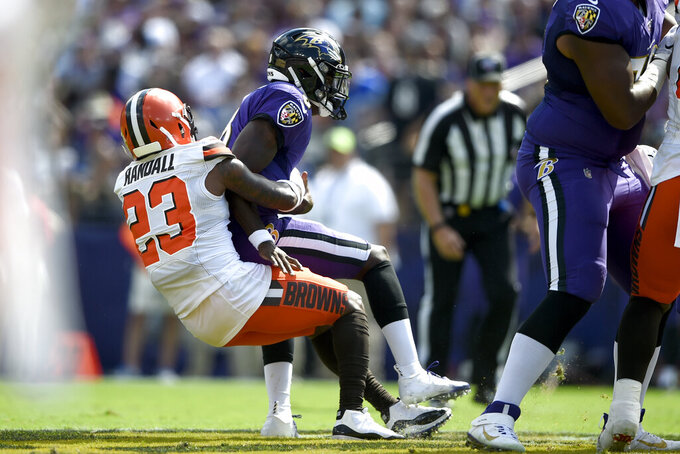 Cleveland Browns strong safety Damarious Randall (23) sacks Baltimore Ravens quarterback Lamar Jackson (8) during the first half of an NFL football game Sunday, Sept. 29, 2019, in Baltimore. (AP Photo/Gail Burton)