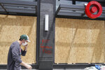 A worker walks past boarded up windows at a Target store in Oakland, Calif., Saturday, May 30, 2020, that was damaged during protests over the death of George Floyd. Floyd died in Minneapolis police custody on May 25. (AP Photo/Jeff Chiu)