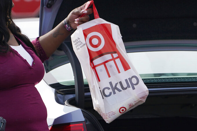 FILE - In this Nov. 5, 2020 file photo, a Target employee places a curbside pickup purchase into the trunk of a customer in Jackson, Miss. The nation's largest retail trade group says Friday, Jan. 15, 2021,  that holiday sales soared 8.3%, far exceeding its forecast even as the coronavirus kept shoppers away from physical stores.  (AP Photo/Rogelio V. Solis, File)