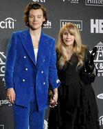 "FILE - Harry Styles, left, and inductee Stevie Nicks pose in the press room at the Rock & Roll Hall of Fame induction ceremony in New York on March 29, 2019. Nicks has become close friends when the former One Direction member since he invited her to perform at one of his concerts in 2017. Since then, they're performed several times together and Styles even previewed his latest album, ""Fine Line,"" for her and some of her friends before it was released in December. (Photo by Charles Sykes/Invision/AP, File)"