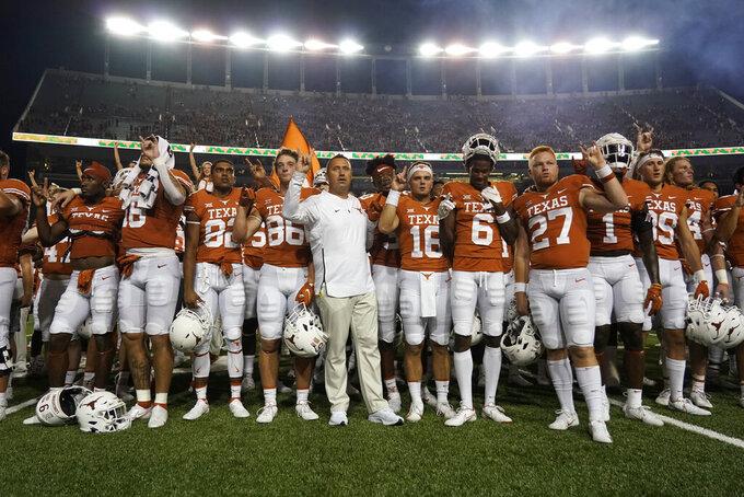"Texas head coach Steve Sarkisian, center, leads his team as they sing ""The Eyes Of Texas"" after an NCAA college football game against Rice on Saturday, Sept. 18, 2021, in Austin, Texas. (AP Photo/Chuck Burton)"