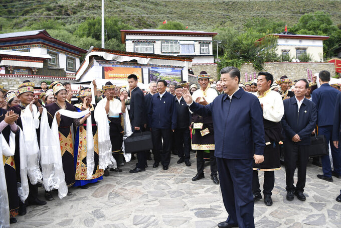 In this photo released by Xinhua News Agency, Chinese President Xi Jinping, waves to villagers while visiting Galai village of Nyingchi, southwest China's Tibet Autonomous Region, Wednesday, July 21, 2021. Chinese leader Xi Jinping has made a rare visit to Tibet as authorities tighten controls over the Himalayan region's traditional Buddhist culture, accompanied by an accelerated drive for economic development. (Shen Hong/Xinhua via AP)