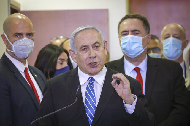 POOL - In this Sunday, May 24, 2020 photo, Israeli Prime Minister Benjamin Netanyahu accompanied by members of his Likud Party in masks delivers a statement before entering the district court in Jerusalem. Netanyahu's fulminating tirade against Israel's legal system on the steps of a Jerusalem courthouse managed to even overshadow the opening of his historic corruption trial. Surrounded by loyal deputies, and with hundreds of impassioned supporters cheering him outside and echoing his charges, Netanyahu's onslaught capped a years-long campaign that has bitterly divided the country and raised fears of irreparably tearing apart the delicate fabric of Israeli society. (AP Photo/Yonatan Sindel/Pool Photo via AP)