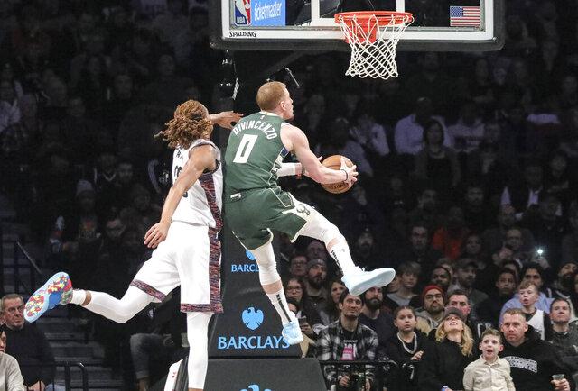 Milwaukee Bucks guard Donte DiVincenzo (0) drives past Brooklyn Nets forward Caris LeVert (22), during a NBA basketball game, Saturday Jan. 18, 2020 in New York. (AP Photo/Bebeto Matthews)