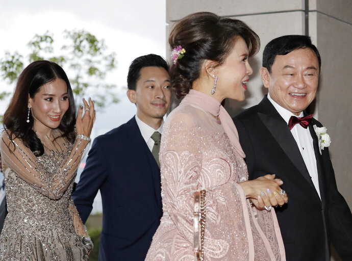 Former Thai Prime Minister Thaksin Shinawatra, right, walks with Princess Ubolratana of Thailand, and followed by his daughter Pintongtha