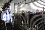 Police watch demonstrators through a closed entrance gate at the Kwun Tong MTR station in Hong Kong, Saturday, Aug. 24, 2019. Chinese police said Saturday they released an employee at the British Consulate in Hong Kong as the city's pro-democracy protesters took to the streets again, this time to call for the removal of