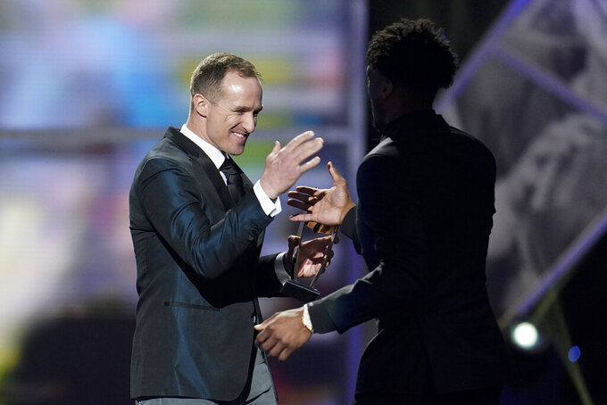 New Orleans Saints quarterback Drew Brees gives Saints' Michael Thomas his AP Offensive Player of the Year award at the NFL Honors football award show Saturday, Feb. 1, 2020, in Miami. (AP Photo/David J. Phillip)