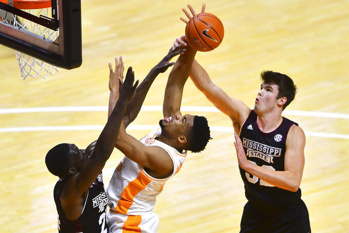 Tennessee forward E.J. Anosike, center, shoots while defended by Mississippi State's Quinten Post, right, during an NCAA college basketball game Tuesday, Jan. 26, 2021, in Knoxville, Tenn. (Brianna Paciorka/Knoxville News Sentinel via AP, Pool)