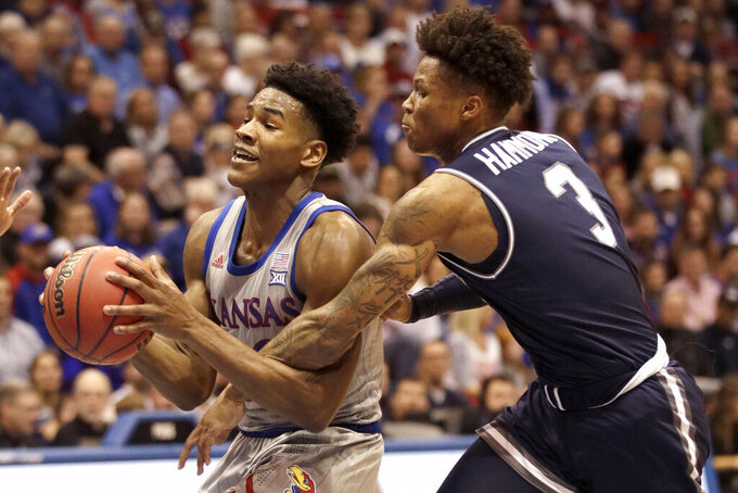 Kansas guard Ochai Agbaji, left, is fouled by Monmouth guard Deion Hammond (3) during the first half of an NCAA college basketball game in Lawrence, Kan., Friday, Nov. 15, 2019. (AP Photo/Orlin Wagner)