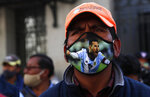 A public transport driver, wearing a protective face mask emblazoned with an image of Lionel Messi, attends a protest demanding an increase in fares because quarantine measures to curb the spread of the new coronavirus have decreased his income, in La Paz, Bolivia, Wednesday, July 1, 2020. (AP Photo/Juan Karita)
