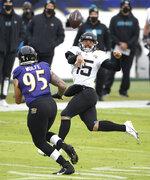 Jacksonville Jaguars quarterback Gardner Minshew II (15) throws a pass as Baltimore Ravens defensive end Derek Wolfe (95) applies pressure during the second half of an NFL football game, Sunday, Dec. 20, 2020, in Baltimore. (AP Photo/Nick Wass)