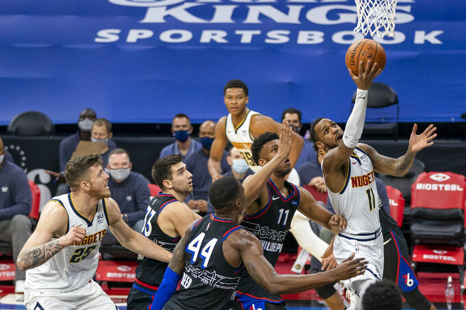 Denver Nuggets' Monte Morris, right, goes up for the shot against Philadelphia 76ers' Tony Bradley, center left, and Paul Reed, center, during the first half of an NBA basketball game, Saturday, Jan. 9, 2021, in Philadelphia. (AP Photo/Chris Szagola)