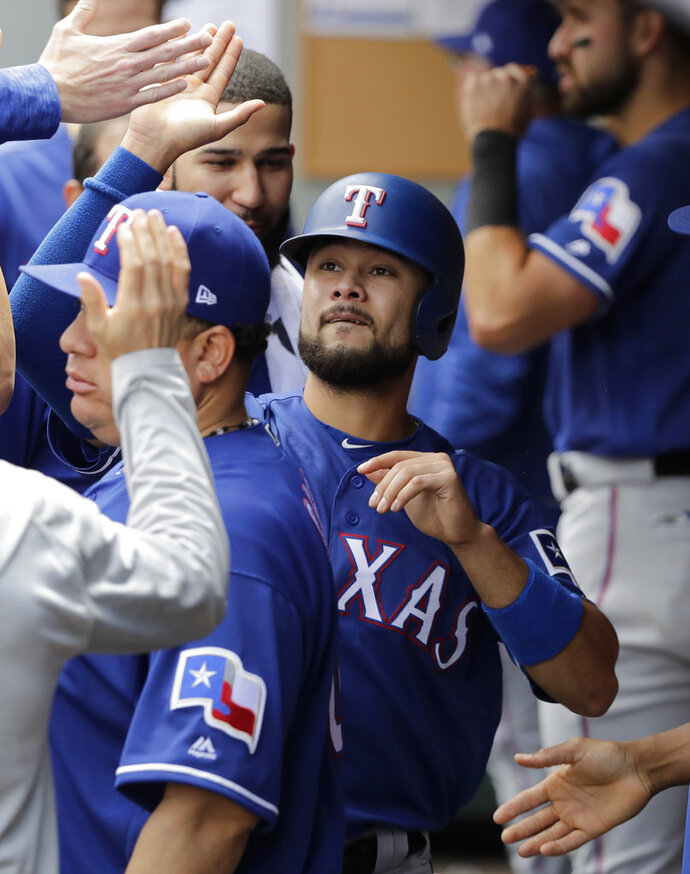 Texas Rangers' Isiah Kiner-Falefa, center, is greeted in the dugout after he scored on an RBI double hit by Delino DeShields during the eighth inning of a baseball game against the Seattle Mariners, Wednesday, May 16, 2018, in Seattle. (AP Photo/Ted S. Warren)