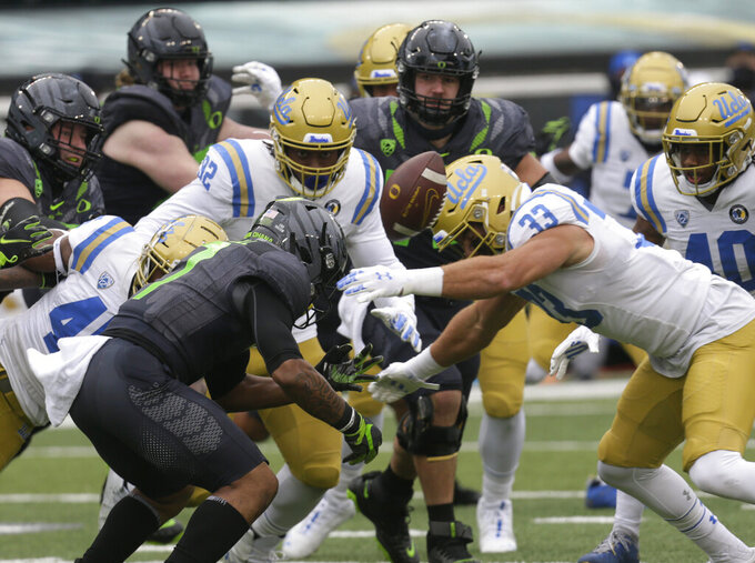 Oregon's CJ Verdell, center, fumbles the ball during the second quarter of an NCAA college football game against UCLA, Saturday, Nov. 21, 2020, in Eugene, Ore. (AP Photo/Chris Pietsch)