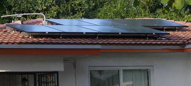 This Sunday, Dec. 23, 2018 photo shows solar panels that were installed through a program called PACE, on Julnor Jean's home in Miami Shores, Fla. While it allows people to make improvements regardless of income, which Jean had little of, it can also leave homeowners in a big financial hole. (Carl Juste/Miami Herald via AP)