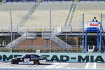 Caesar Bacarella (90) passes empty seats during a NASCAR Xfinity Series auto race Saturday, June 13, 2020, in Homestead, Fla. (AP Photo/Wilfredo Lee)