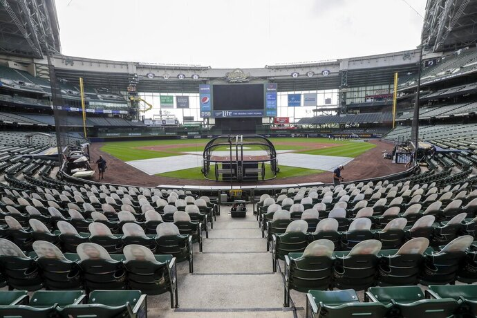 FILE - In this Friday, July 31, 2020, file photo, fan cutouts sit in seats behind home plate at Miller Park after it was announced that the baseball game between the Milwaukee Brewers and Cardinals in Milwaukee, was postponed after two Cardinals employees tested positive for the coronavirus. One more player and three staff members with the Cardinals have tested positive for the coronavirus, leading to the postponement of their game on Saturday against the Brewers, according to a person familiar with the situation. (AP Photo/Morry Gash, File)